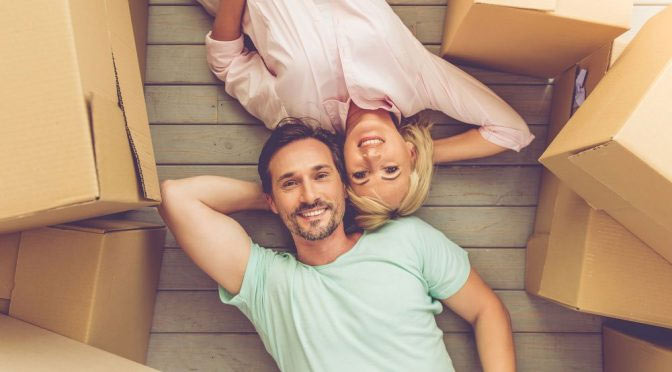 A couple lying together while surrounded by cardboard boxes