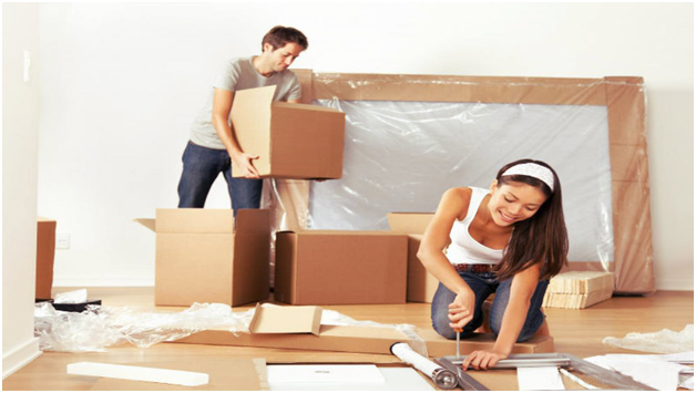 A man keeping boxes together and a women dismantling a table