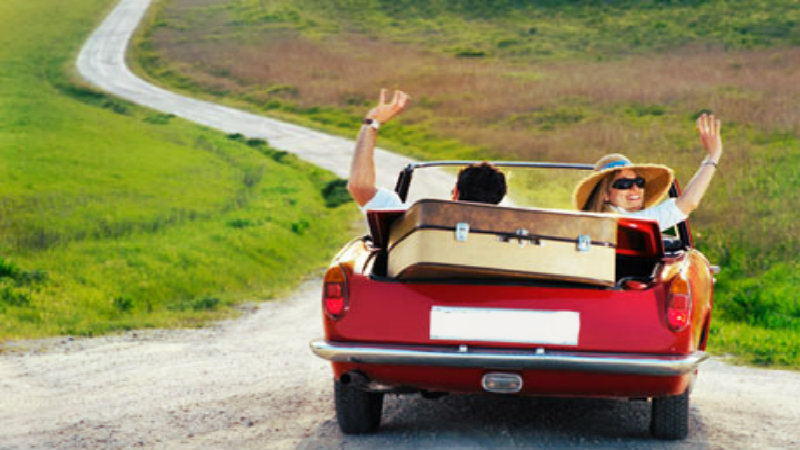 A couple going on an adventure in a small red car