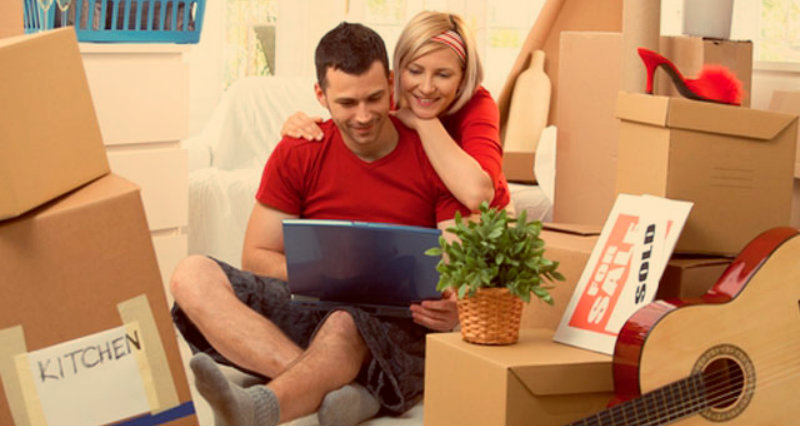 A couple sitting together beside a pile of cardboard boxes
