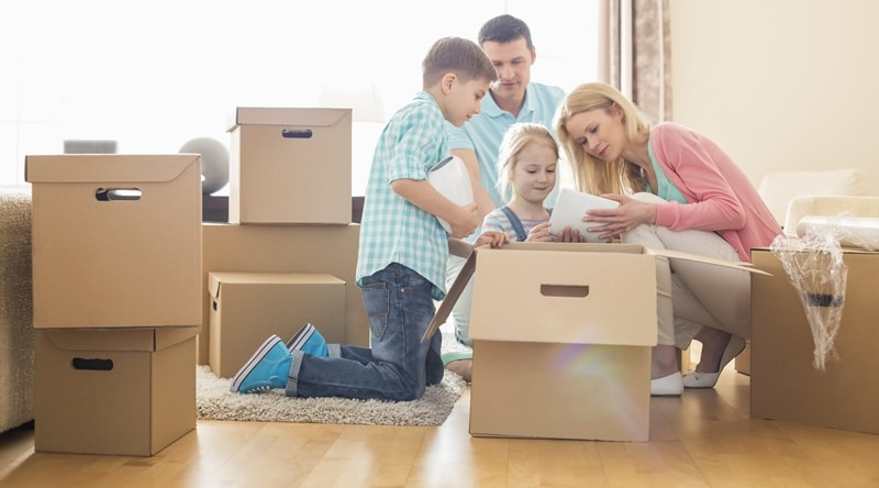 A Family of 4 Unpacking Cardboard Box Together