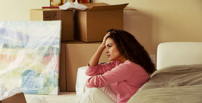 A women sitting beside the bed, stressing about a move