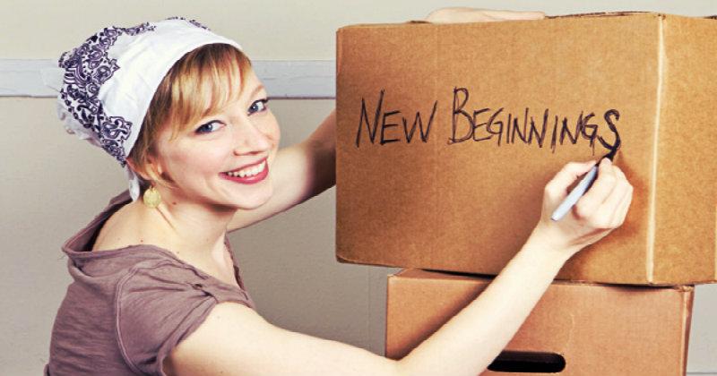 A Women writing 'New Beginnings' on a cardboard box