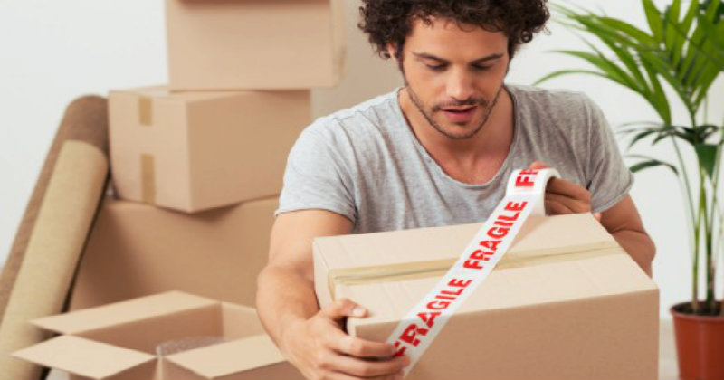 a guy with curly hairs packing a cardboard box with fragile tape