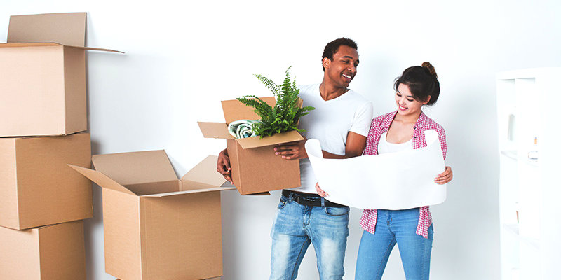 happy couple holding cardboard box and a checklist