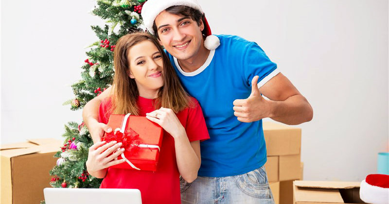 happy couple holding gift items with packed boxes kept on floor