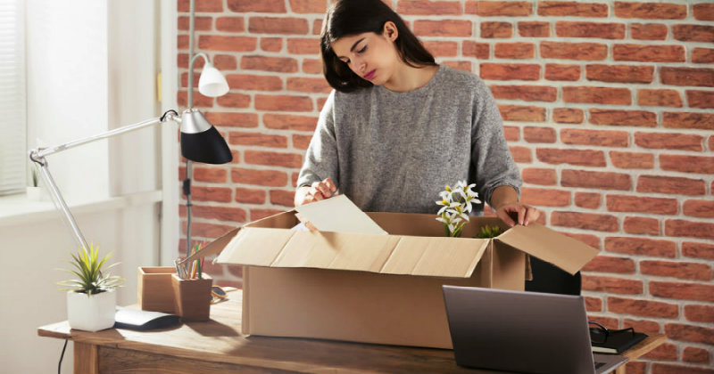 young beautiful woman packing things in a box