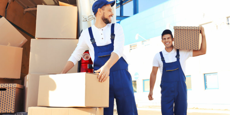 two men in uniform lifting corrugated boxes