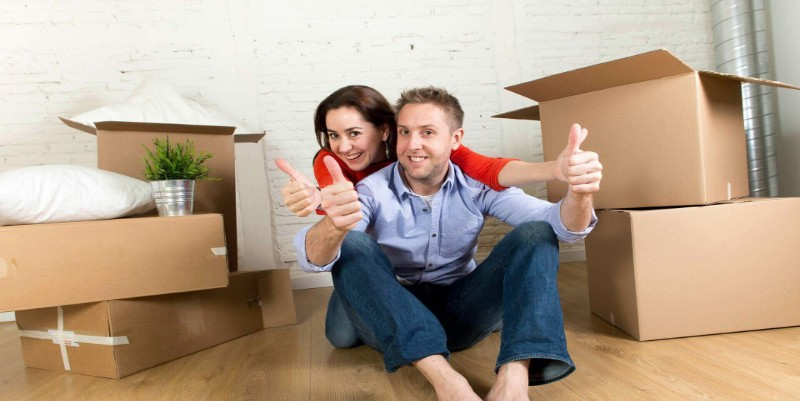 a man and woman sitting on floor alongside packed boxes