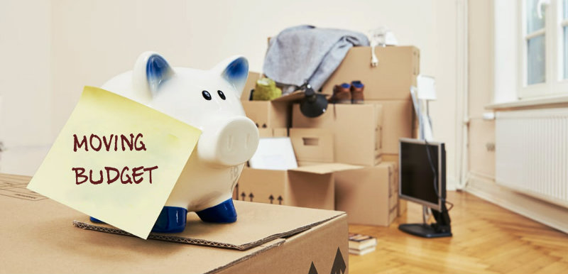 Piggy bank kept on the packed boxes with moving budget slip on it