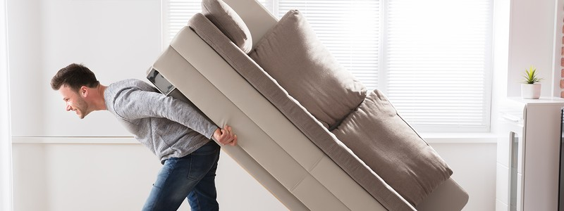 a person is trying to move a couch alone