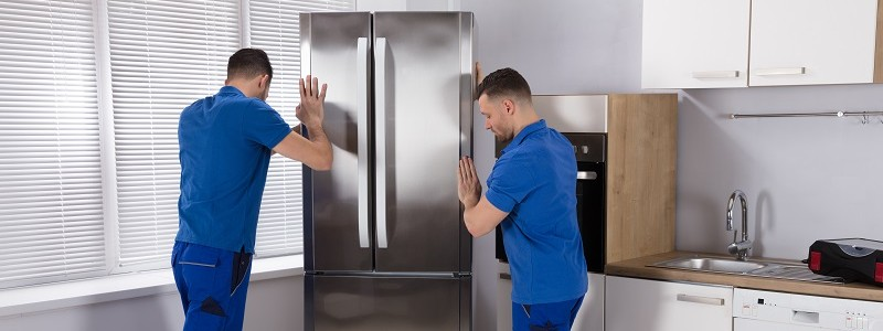 two young professionals trying to lift a heavy refrigerator