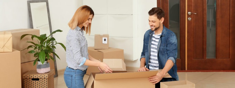 young couple packing a cardboard box