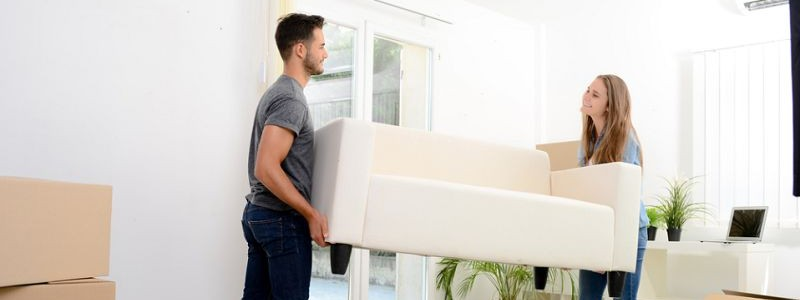 Young couple trying to relocate a couch