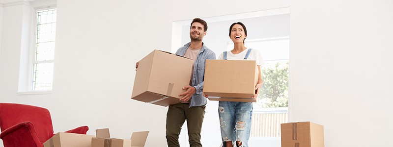 couple holding cardboard boxes inside of their new house