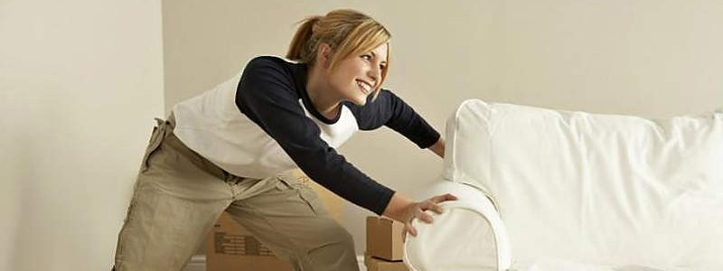 Young woman trying to relocate a couch
