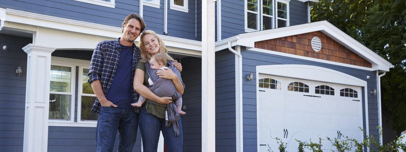couple with their child standing outside of their house