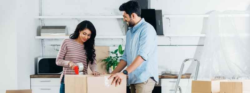 young couple packing up a cardboard box