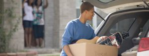 young man putting the household on a car