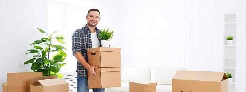 young man holding a couple of cardboard boxes