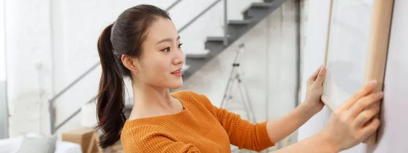 young beautiful woman hanging a photo frame on a wall